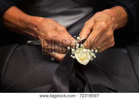 Hands Of Mother Who Sew Flowers On The Groom's Tie