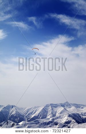 Sunlight Mountain With Clouds And Silhouette Of Paraglider