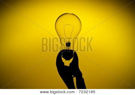 A Silhouette Of A Clear Light Bulb Held In A Grip On A Yellow Glow Background