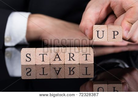 Businessman Arranging Startup Blocks On Desk