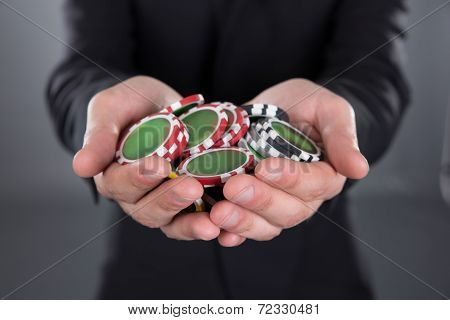 Businessman Holding Poker Chips In Cupped Hands