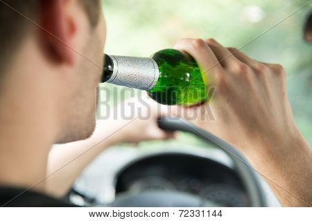 Man Drinking Alcohol While Driving Car