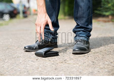 Man Picking Up Fallen Wallet
