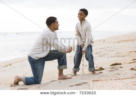 African-American father and son playing on beach