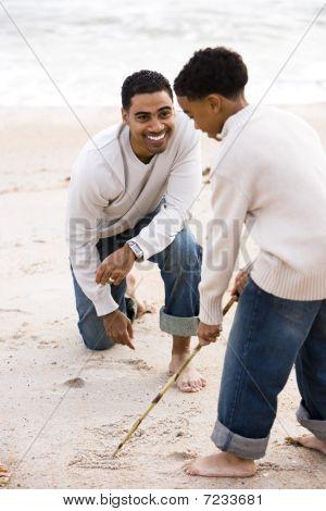 Afroamerikaner Vater und Sohn spielen am Strand