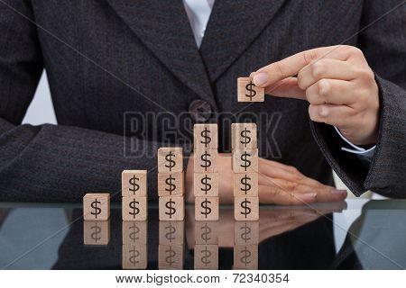 Businesswoman Stacking Dollar Blocks