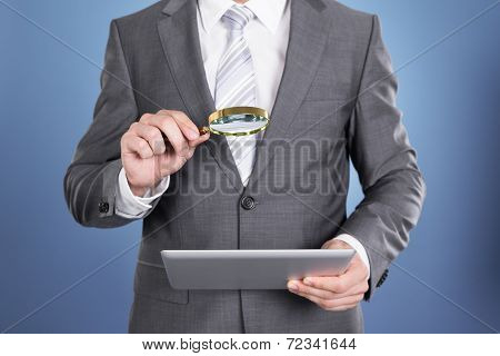 Auditor Holding Magnifying Glass And Tablet