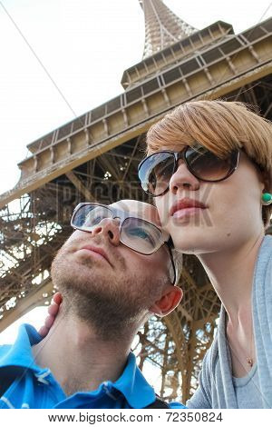 Side View Of A Young Couple Embracing With Eiffel Tower