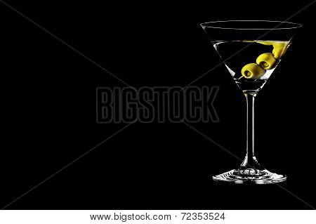 Martini glass with olives on a black background