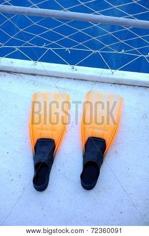 Orange flippers on boat dock