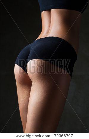 Beautiful fit, sexy female body on dark gray