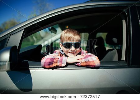 little boy driving fathers car