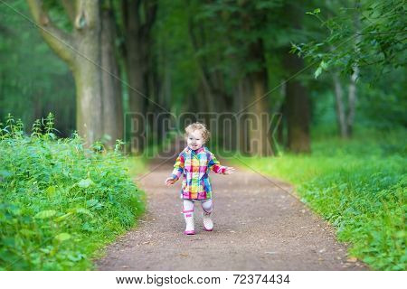 Cute Baby Girl In Rubber Rain Boots Walking In A Rainy Park