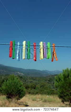 Multicolored clothespin hanged on a blue cord
