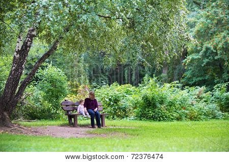 Grandmother And Baby Girl Relaxing In A Park On A Bench Under A Beautiful Tree On A Sunny Autumn Day