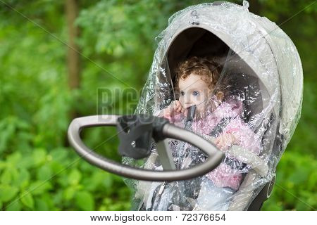 Little Baby Girl Sitting In A Stroller Under A Rain Cover On A Cold Autumn Day