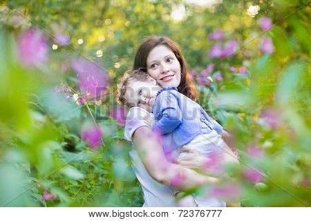 Young Pregnant Mother Holding Her Tired Baby Daughter In A Park At Sunset