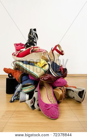 Big pile of colorful woman shoes.