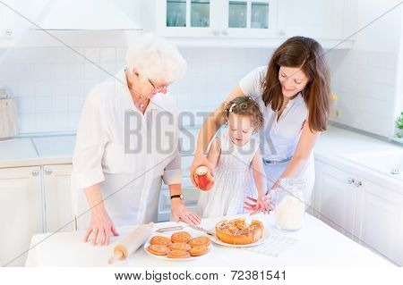 Great Grandmother Baking An Apple Pie With Her Family, Young Granddaughter And A Cute Curly Toddler