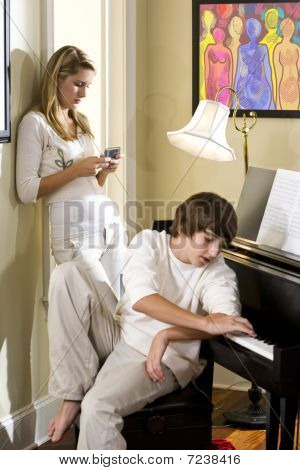 Teenager brother and sister at home by piano