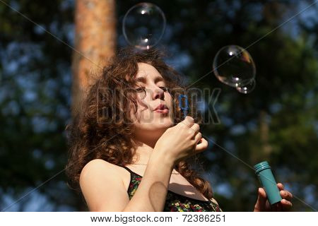 Young Pretty Woman Blowing Soap Bubbles