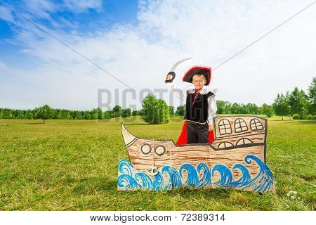 Boy in pirate hat with sword stands on carton ship