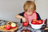 foto of pie-in-face  - Adorable little boy helping and baking apple pie in home - JPG