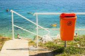 image of segregation  - Orange trash bin near the sea beach - JPG