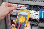 picture of fuse-box  - Cropped image of male electrician examining fusebox with digital insulation resistance tester - JPG