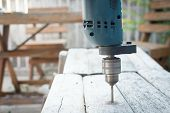 pic of hand drill  - Electric drill drilling wood table it made hole for carpenter - JPG