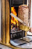 picture of kababs  - Cook slices shawarma from the spit for doner kababs in Mardin Turkey - JPG