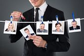 stock photo of clotheslines  - Midsection of businessman selecting candidate from clothesline against gray background - JPG
