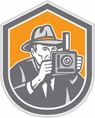 image of fedora  - Illustration of a photographer wearing fedora hat shooting with vintage bellows camera set inside shield crest on isolated background done in retro style - JPG