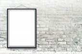 stock photo of wall painting  - Blank vertical painting poster in black frame hanging on white brick wall - JPG