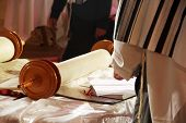 image of torah  - Torah scrolls; is on the table; people in Talas wooden handles close up