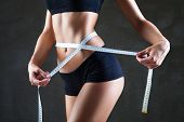 foto of measurements  - Athletic slim woman measuring her waist by measure tape after a diet over dark gray background - JPG
