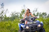 picture of four-wheel drive  - Elegant woman riding extreme quadrocycle in summer fields - JPG