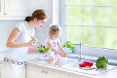 stock photo of young baby  - Young Beautiful Mother And Her Cute Curly Toddler Daughter Washing Vegetables Together In A Kitchen