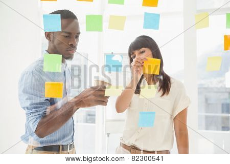Concentrated coworkers looking at sticky notes in the office