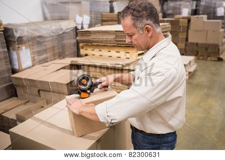 Warehouse worker preparing a shipment in a large warehouse