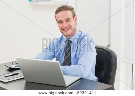 Cheerful stylish businessman using laptop in his office