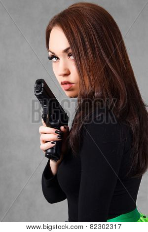 Portrait Of A Young Attractive Woman With A Gun