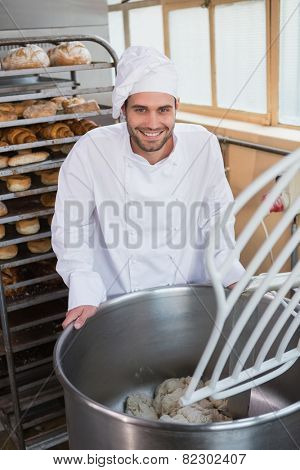 Smiling baker preparing dough in industrial mixer at the bakery