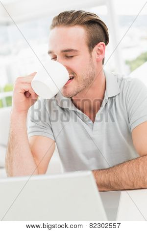 Cheerful businessman using laptop while drinking in his office