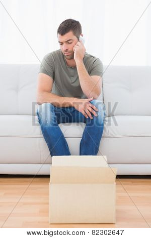 Casual man at the phone sitting on a sofa looking a boxe