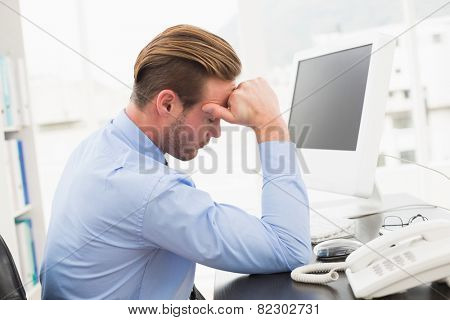 Tired businessman working with computer in his office