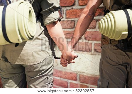 Hitch hiking couple standing holding hands on the road against red brick wall