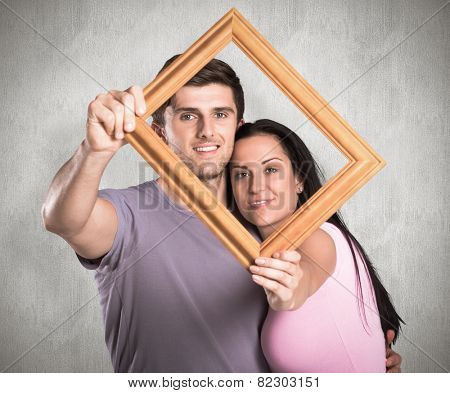 Young couple holding up frame against weathered surface