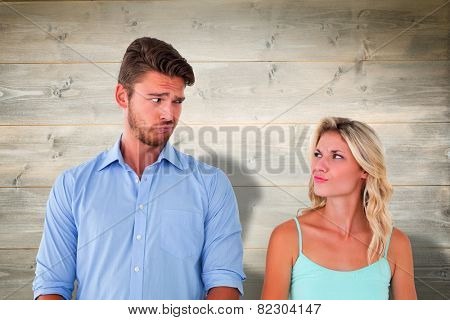 Young couple making silly faces against bleached wooden planks background
