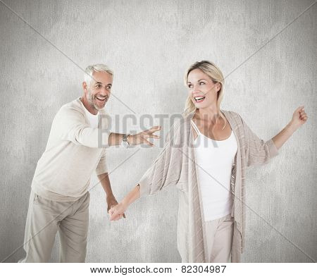 Happy couple messing about together against white background
